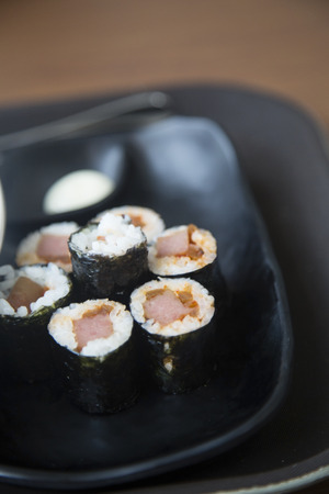 Korean style sushi served in the black dish