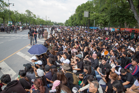 soldiers: People wearing black clothes are sitting on the road in front of Royal Palace in Bangkok, waiting funeral procession with body of his majesty king of Thailand Rama IX, Bhumibol Adunjadet