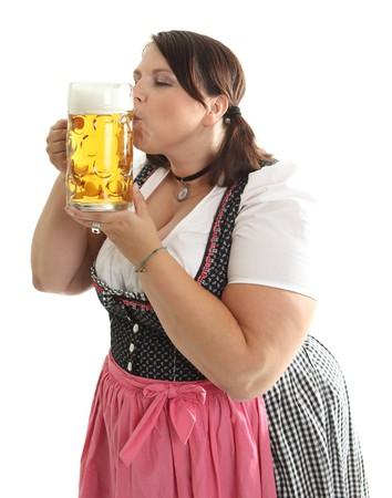 A bavarian girl kissing Oktoberfest beer mug, dressed in a traditional dirndl