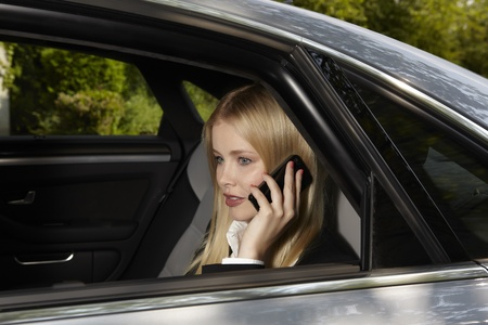blond haired: Woman on the phone in a car Stock Photo