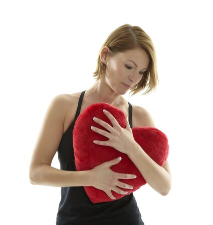 constancy: Woman cuddling with red heart pillow