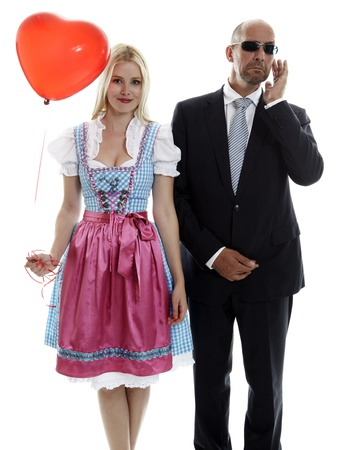 Woman in Dirndl with red heart balloon and Bodyguard photo