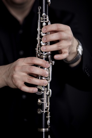 Clarinet player in front of black background photo