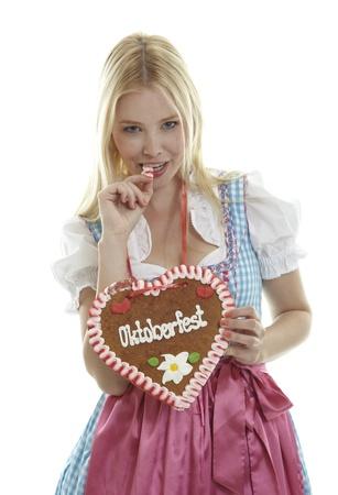 Woman bites in a German Gingerbread heart Standard-Bild