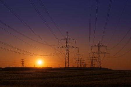 Sunset with Wind Turbines behind Power Lines and a group of Power Towers Standard-Bild