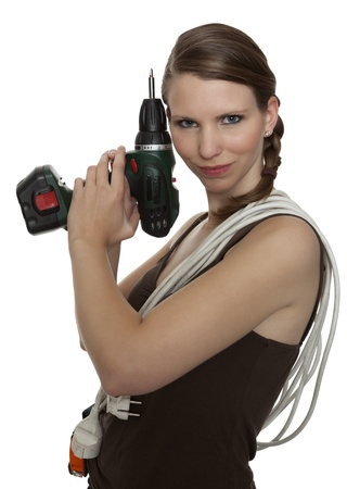 Young craftswoman with a power drill in front of white background Stock Photo