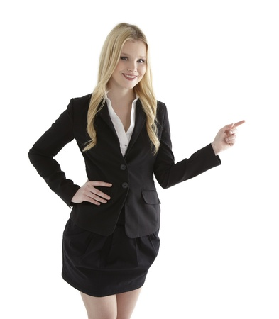 Beautiful young businesswoman pointing at white copyspace photo