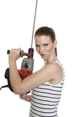 servicewoman: Young craftswoman with a power drill in front of white background Stock Photo