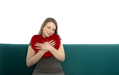 Beautyful young and smiling woman sitting on a sofa embracing heart shaped pillow with her hands photo