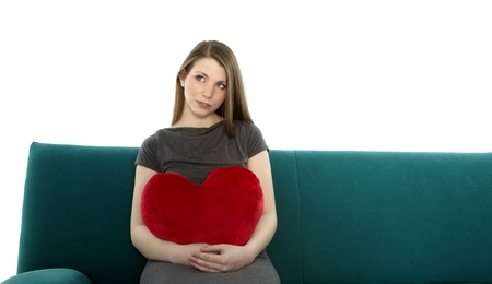Beautyful young woman smiling and sitting on a sofa with heart shaped pillow in her hand photo