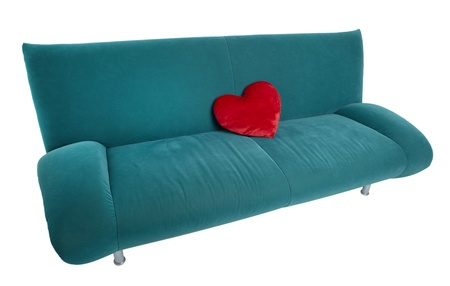 Green sofa with red heart shaped pillow lying on the middle of the couch photo