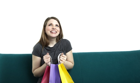 Portrait of young happy smiling woman sitting on a sofa with shopping bags Stock Photo - 18551096