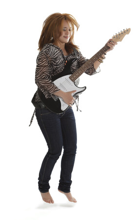glam rock: Young rock lady jumping with an electric guitar