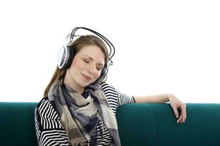 Beautiful young smiling woman sitting on a sofa and listens to music with headphones on her head with eyes closed