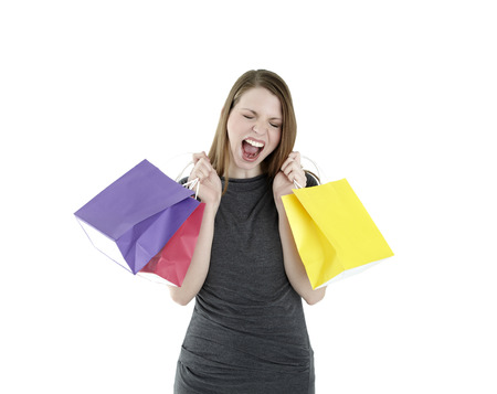 Excited shopping woman shouting with shopping bags photo