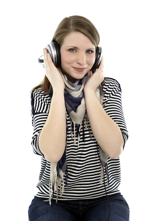 Beautiful young smiling woman listens to music with headphones on her head photo