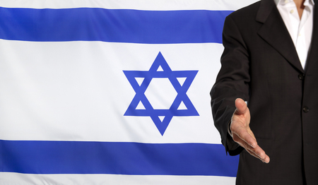 courteous: Businessman with an open hand waiting for a handshake concept for business with the Israel flag in the background Stock Photo
