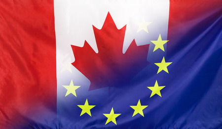 Canada and European Union relations concept with diagonally merged real fabric flags