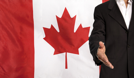 courteous: Businessman with an open hand waiting for a handshake concept for business with the Canada flag in the background
