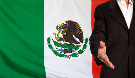 courteous: Businessman with an open hand waiting for a handshake concept for business with the Mexico flag in the background