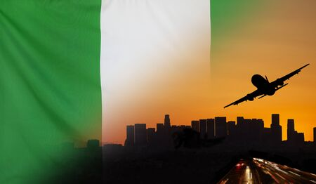 Travel and transport concept with skyline silhouette, highway traffic and airplane at sunset merged with real fabric flag of Nigeria