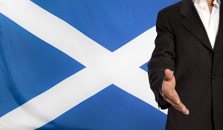 courteous: Businessman with an open hand waiting for a handshake concept for business with the Scotland flag in the background Stock Photo
