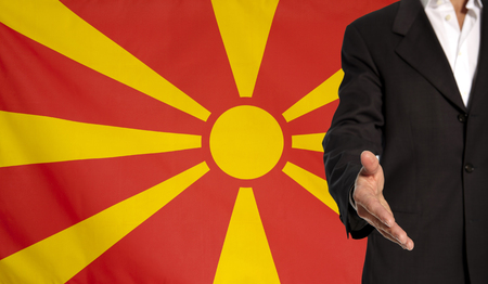 Businessman with an open hand waiting for a handshake concept for business with the Macedonia flag in the background Stock Photo