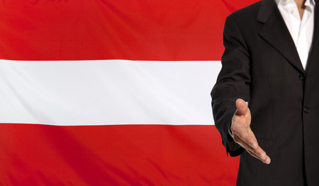 courteous: Businessman with an open hand waiting for a handshake concept for business with the Austria flag in the background
