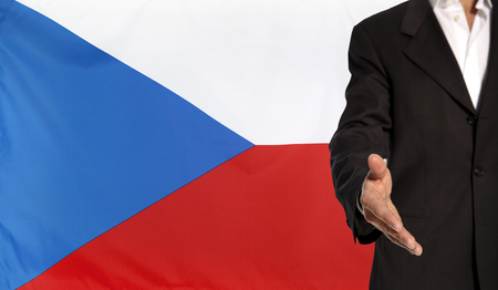 courteous: Businessman with an open hand waiting for a handshake concept for business with the Czech Republic flag in the background Stock Photo