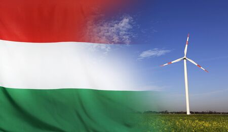 Concept clean energy with flag of Hungary merged with wind turbine in a blue sunny sky and green grass with flowers