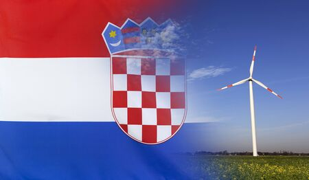 merged: Concept clean energy with flag of Croatia merged with wind turbine in a blue sunny sky and green grass with flowers