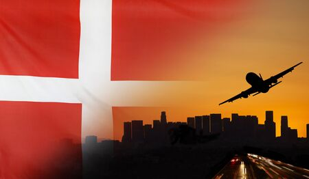Travel and transport concept with skyline silhouette, highway traffic and airplane at sunset merged with real fabric flag of Denmark