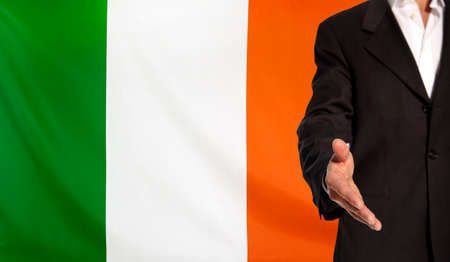 republic of ireland: Businessman with an open hand waiting for a handshake concept for business with the Republic of Ireland flag in the background Stock Photo