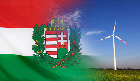 Concept clean energy with flag of Hungary Coat of Arms merged with wind turbine in a blue sunny sky and green grass with flowers