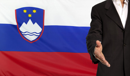courteous: Businessman with an open hand waiting for a handshake concept for business with the Slovenia flag in the background