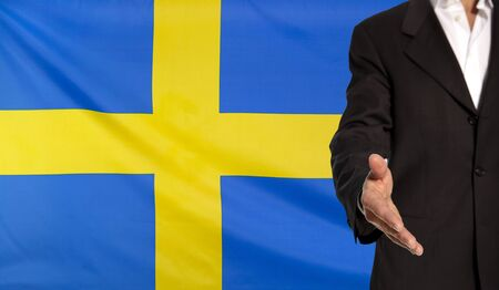 Businessman with an open hand waiting for a handshake concept for business with the Sweden flag in the background