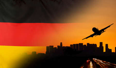 merged: Travel and transport concept with skyline silhouette, highway traffic and airplane at sunset merged with real fabric flag of Germany