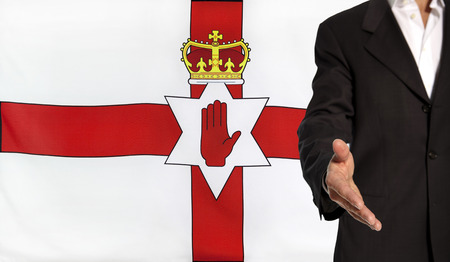 Businessman with an open hand waiting for a handshake concept for business with the Northern Ireland flag in the background