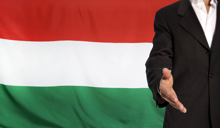 courteous: Businessman with an open hand waiting for a handshake concept for business with the Hungary flag in the background
