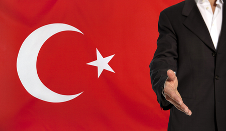 Businessman with an open hand waiting for a handshake concept for business with the Turkey flag in the background