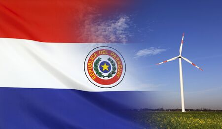 Concept clean energy with flag of Paraguay merged with wind turbine in a blue sunny sky and green grass with flowers Stock Photo