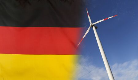merged: Concept clean energy with flag of Germany merged with wind turbine in a blue sunny sky Stock Photo