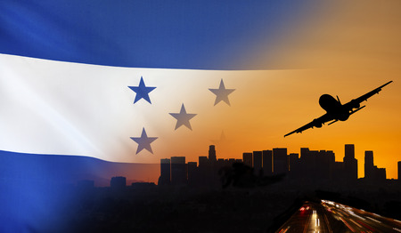Travel and transport concept with skyline silhouette, highway traffic and airplane at sunset merged with real fabric flag of Honduras