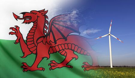 Concept clean energy with flag of Wales merged with wind turbine in a blue sunny sky and green grass with flowers