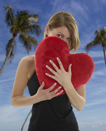Young beautiful woman hiding behind a red heart shaped pillow with palm trees and blue sky in the background photo