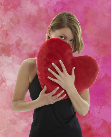 Young beautiful woman hiding behind a red heart shaped pillow with a red aquarell painted background photo