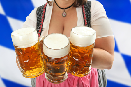 cleavage: Bavarian Waitress holding Oktoberfest Beer in front of her cleavage with a bavarian flag in the background