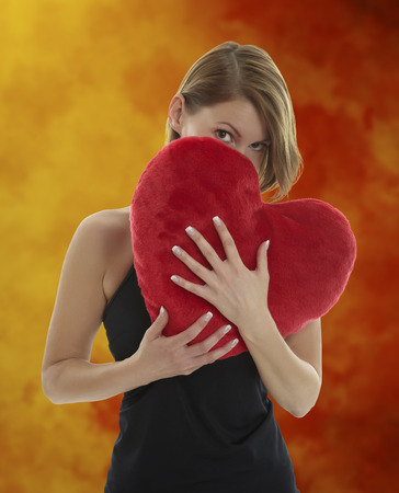 Young beautiful woman hiding behind a red heart shaped pillow with a orange and red structured blurred background photo