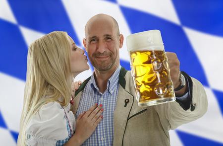 cheek to cheek: Bavarian Oktoberfest Couple man holding a beer mug and gets kissed on his cheek Stock Photo