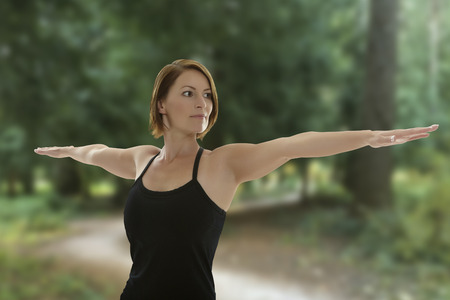 Young beautiful woman doing yoga asana warrior pose with trees in the background Stock Photo